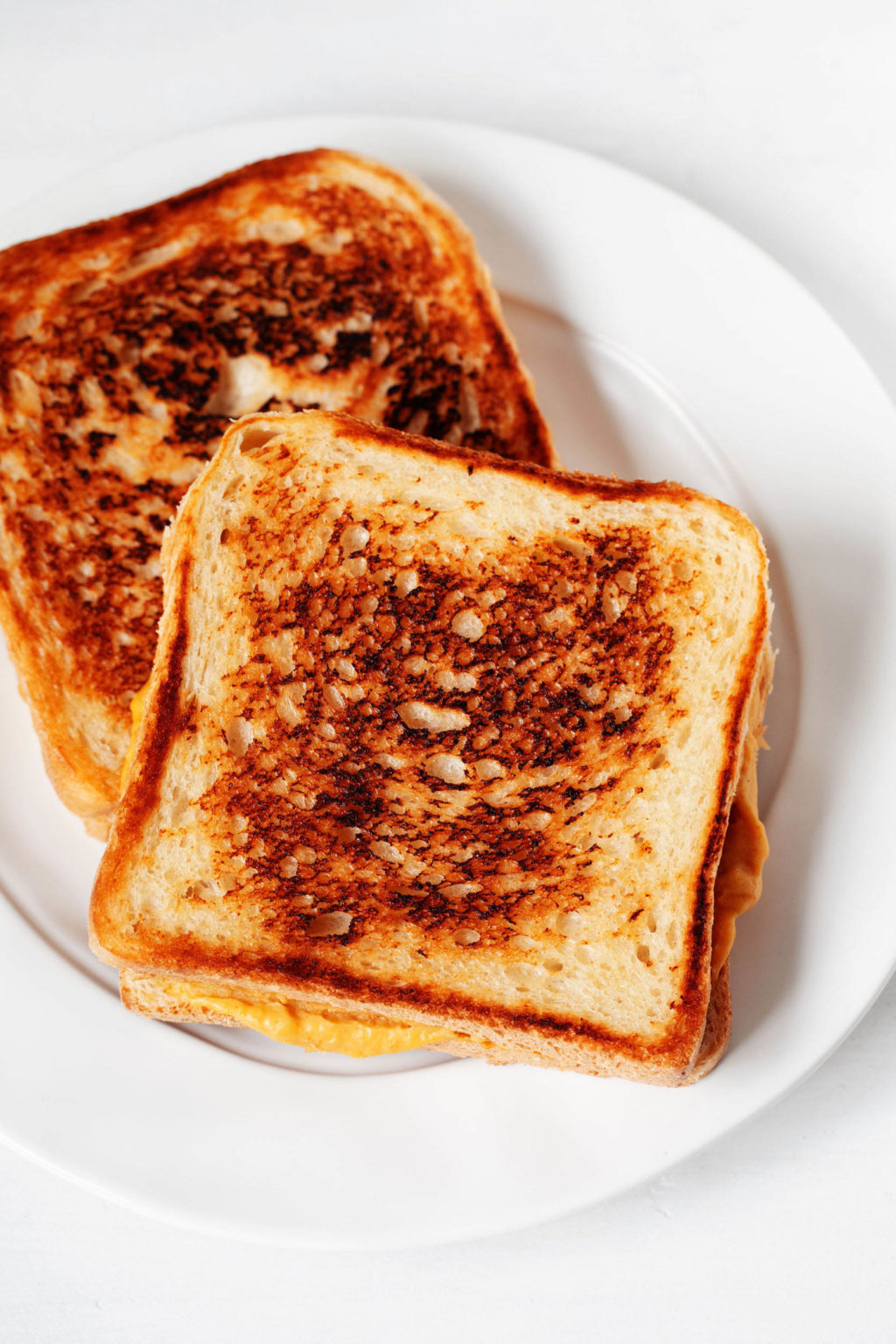A toasted vegan grilled cheese sandwich is resting on a rimmed, white plate. The plate is resting on a white surface.
