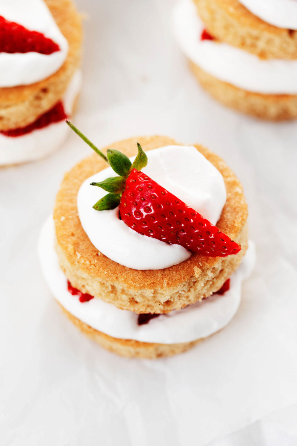 An overhead image of vegan strawberry shortcakes that are resting on a white surface. They've been decorated with whipped cream and slivers of fresh strawberry.