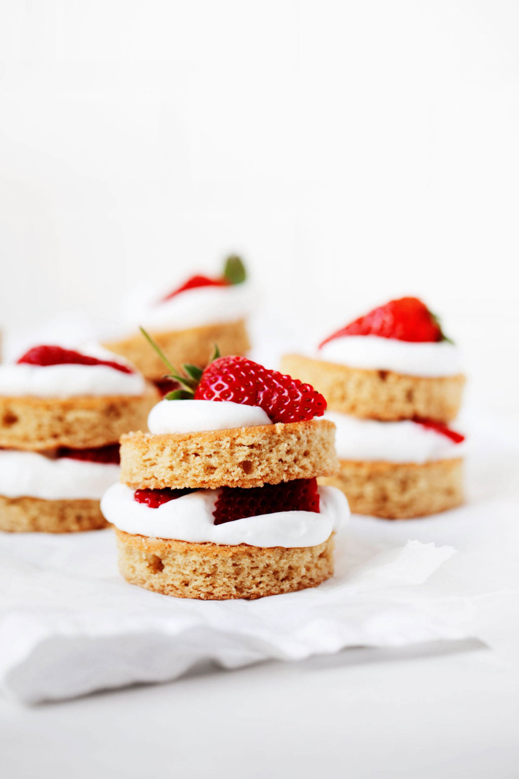 Four vanilla cakes have been stuffed with strawberries and cream. They're resting on a white sheet of crumpled parchment paper.