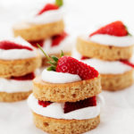 Four stacks of vegan strawberry shortcake are lined up on a sheet of white parchment paper.