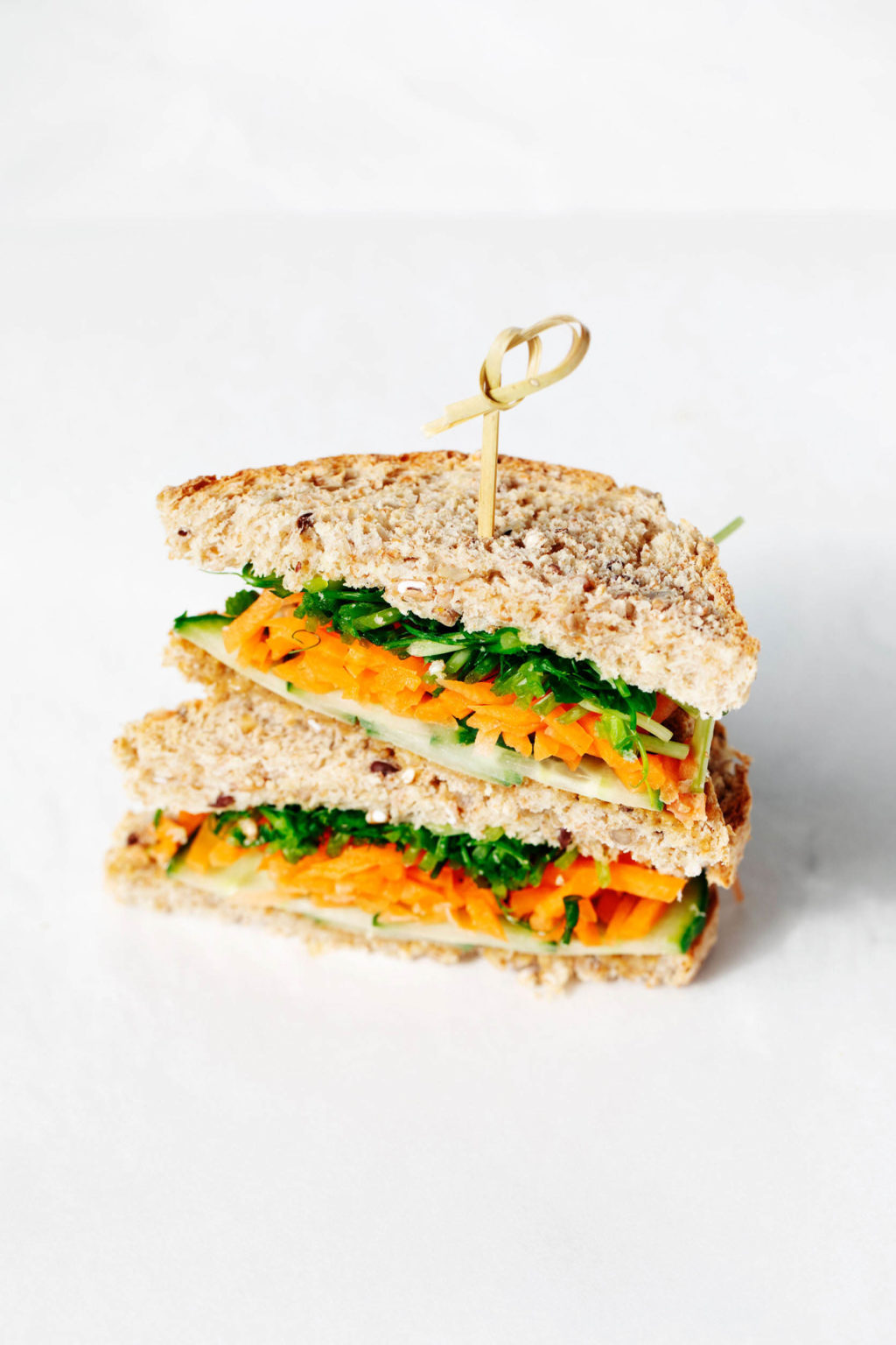 A whole grain, vegan miso tahini sandwich with fresh vegetables is stacked on a white surface.