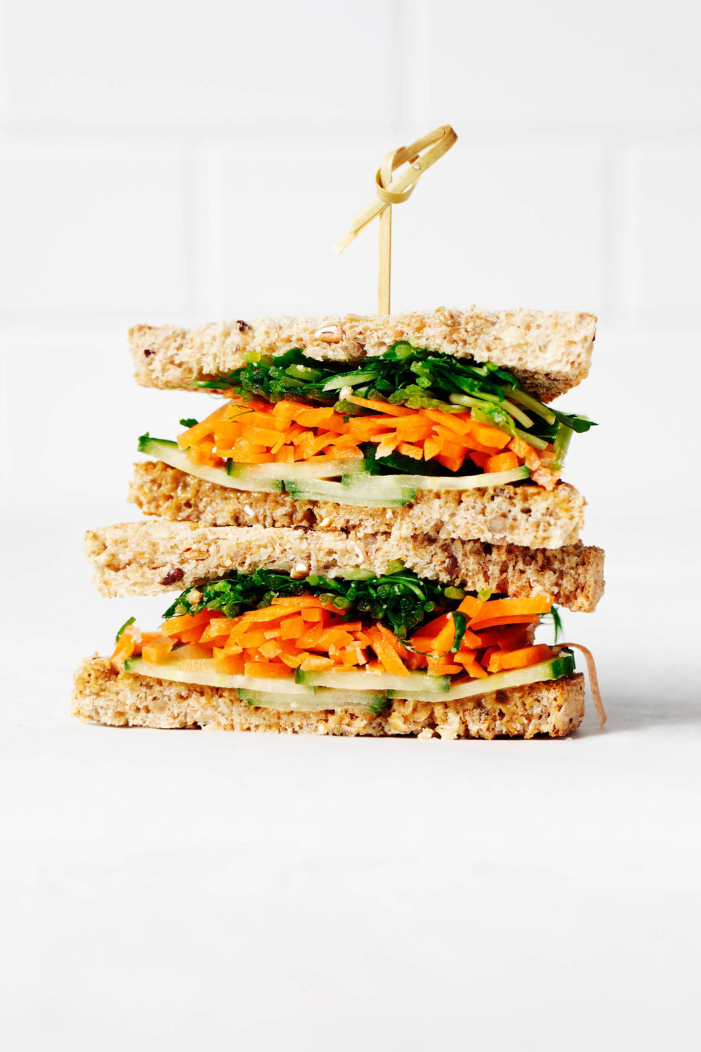 A sandwich has been assembled with layers of carrot, sprouts, and cucumber slices. It's resting on a white surface against a white brick backdrop.