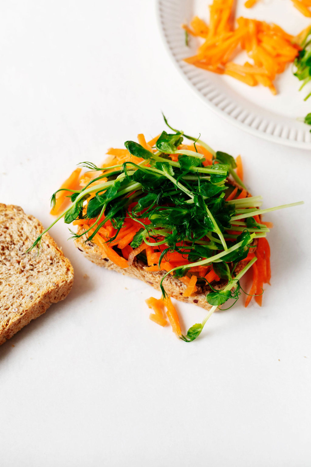 Two slices of whole grain bread are on a white surface. One slice has been piled with carrots and sprouts.
