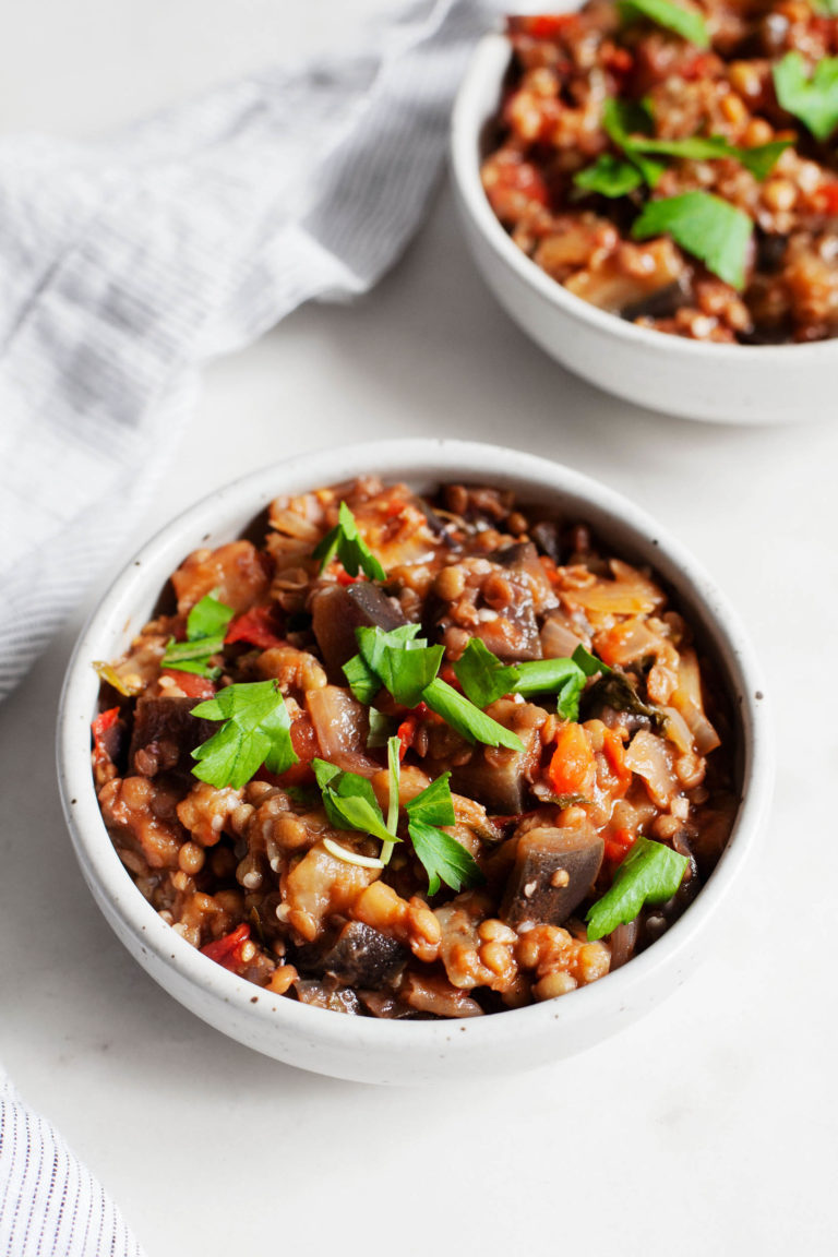 An image of stewed eggplant tomato lentils with fresh parsley on top.