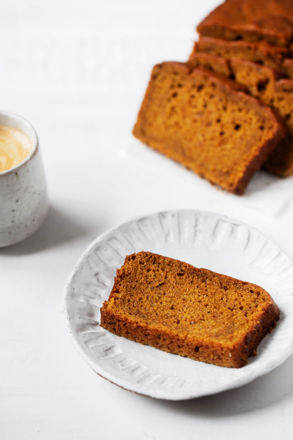 A piece of pumpkin bread, ready for snacking along with a frothy latte. And slices of more bread in the background.