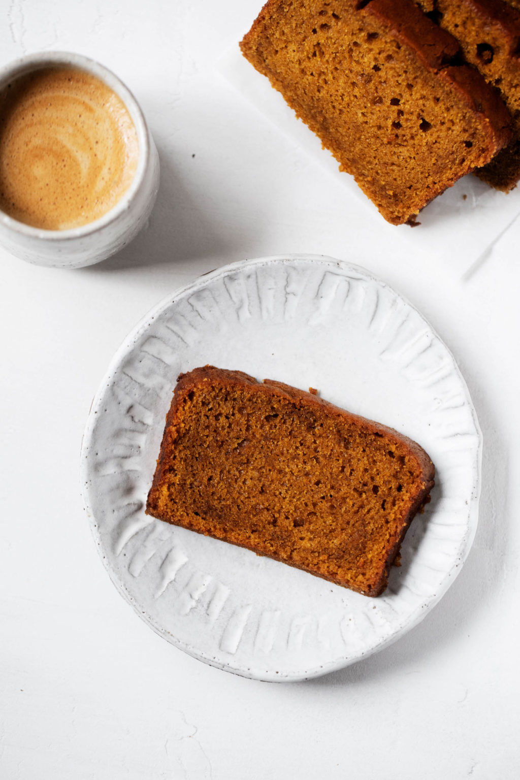 An overhead shot of a slice of vegan pumpkin bread, served with a warm latte.