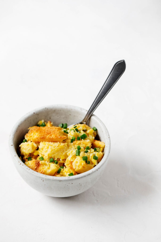 A small bowl of soft, vegan corn pudding. Ready to eat, with a serving spoon