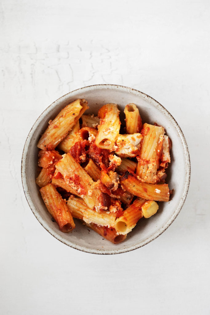Overhead view of a bowl of vegan baked rigatoni, made with tomatoes and ricotta with tofu and cashew nuts.