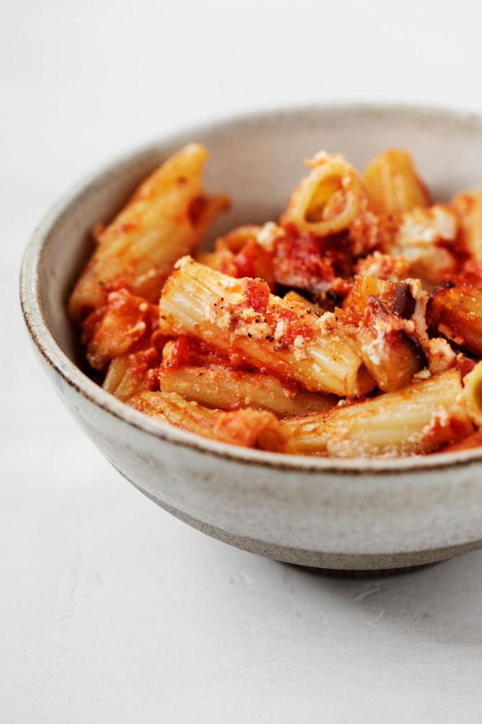 Close up of cooked vegan rigatoni, with cashew tofu ricotta and juicy tomatoes.