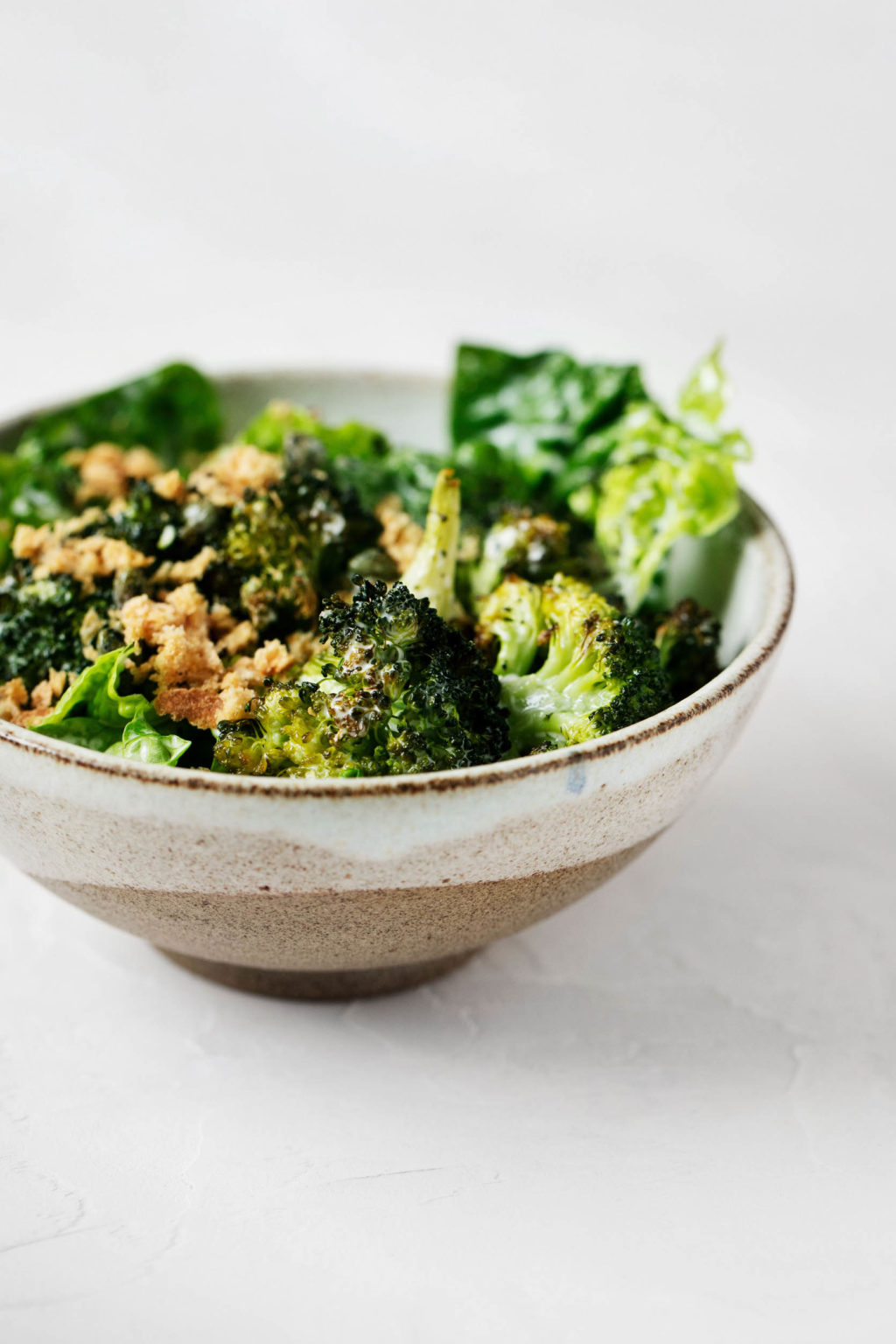 An angled, sideways image of a vegan Caesar salad, made with crispy broccoli, fresh bread crumbs, and vegan parmesan.