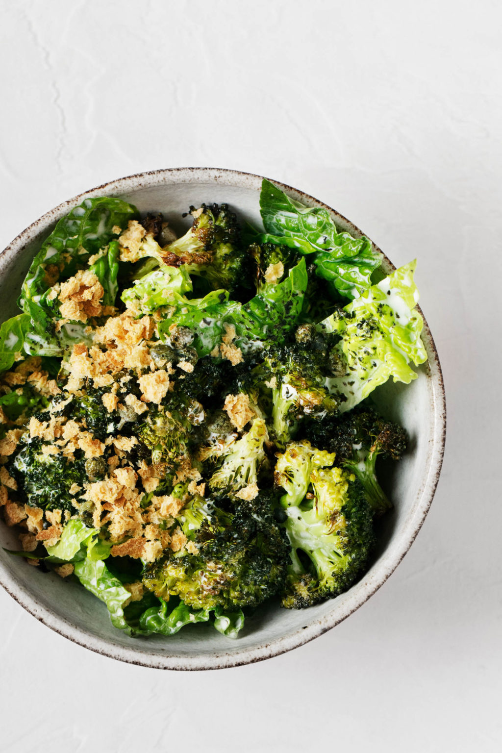 An overhead shot of a bright green dish of crispy roasted broccoli Caesar salad.