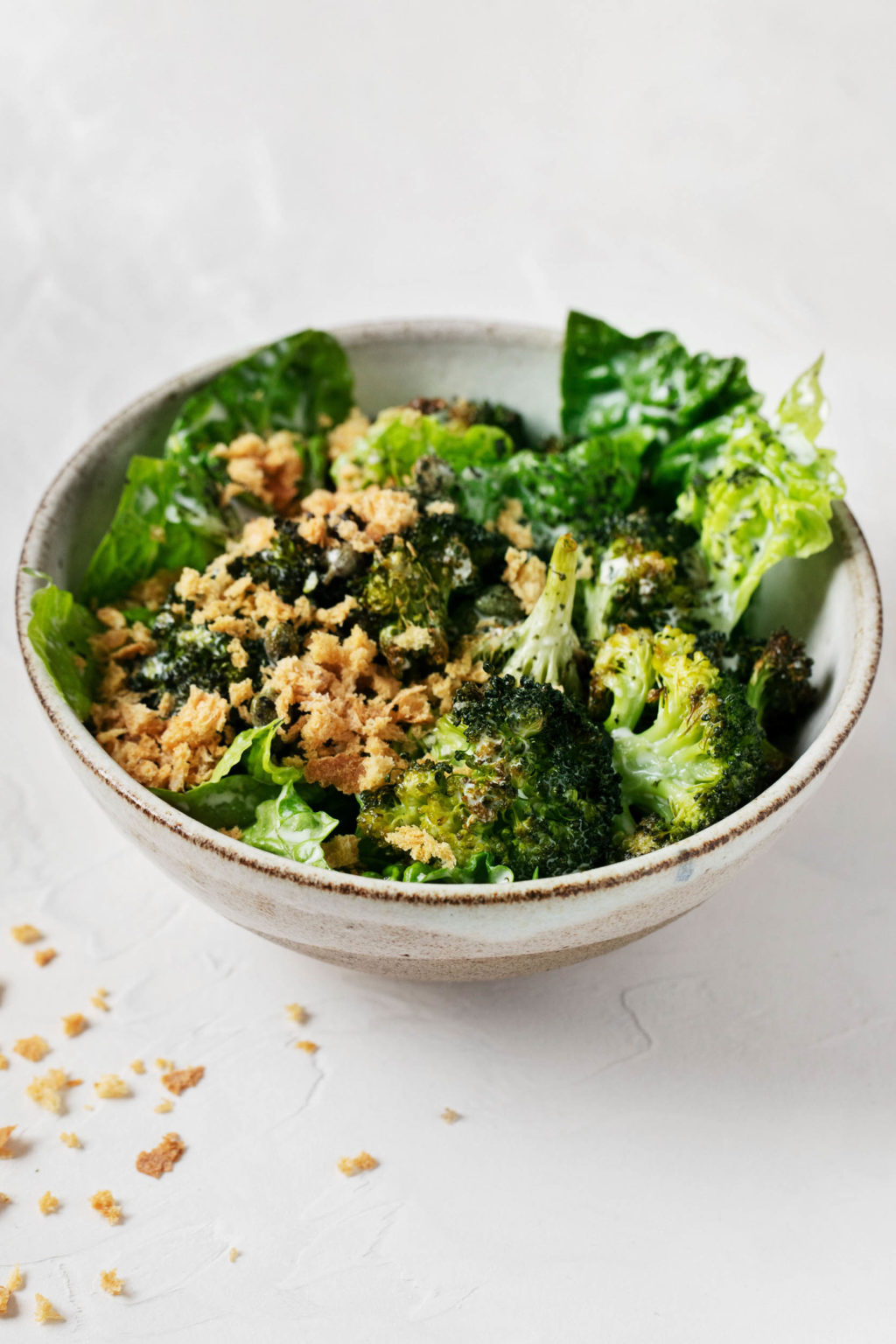 An angled shot of a vegan crispy broccoli Caesar salad, with fresh bread crumbs scattered over the marble surface.