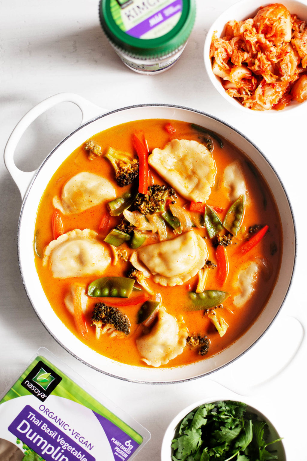 A bowl of red curry dumpling soup, made with the Nasoya brand kimchi as an accompaniment.