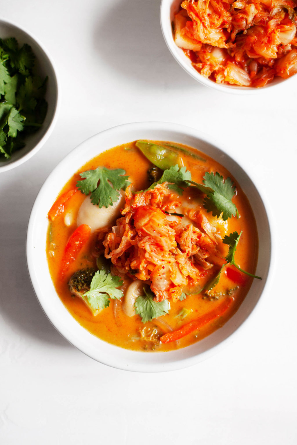 A bowl of red curry soup, garnished with a generous ball of kimchi.