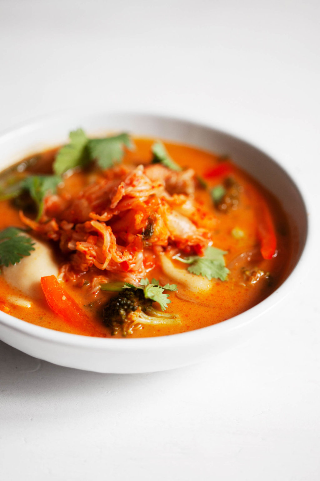 An angled photograph of a vegan red curry soup, made with plump, plant-based dumplings and garnished with a mound of kimchi.
