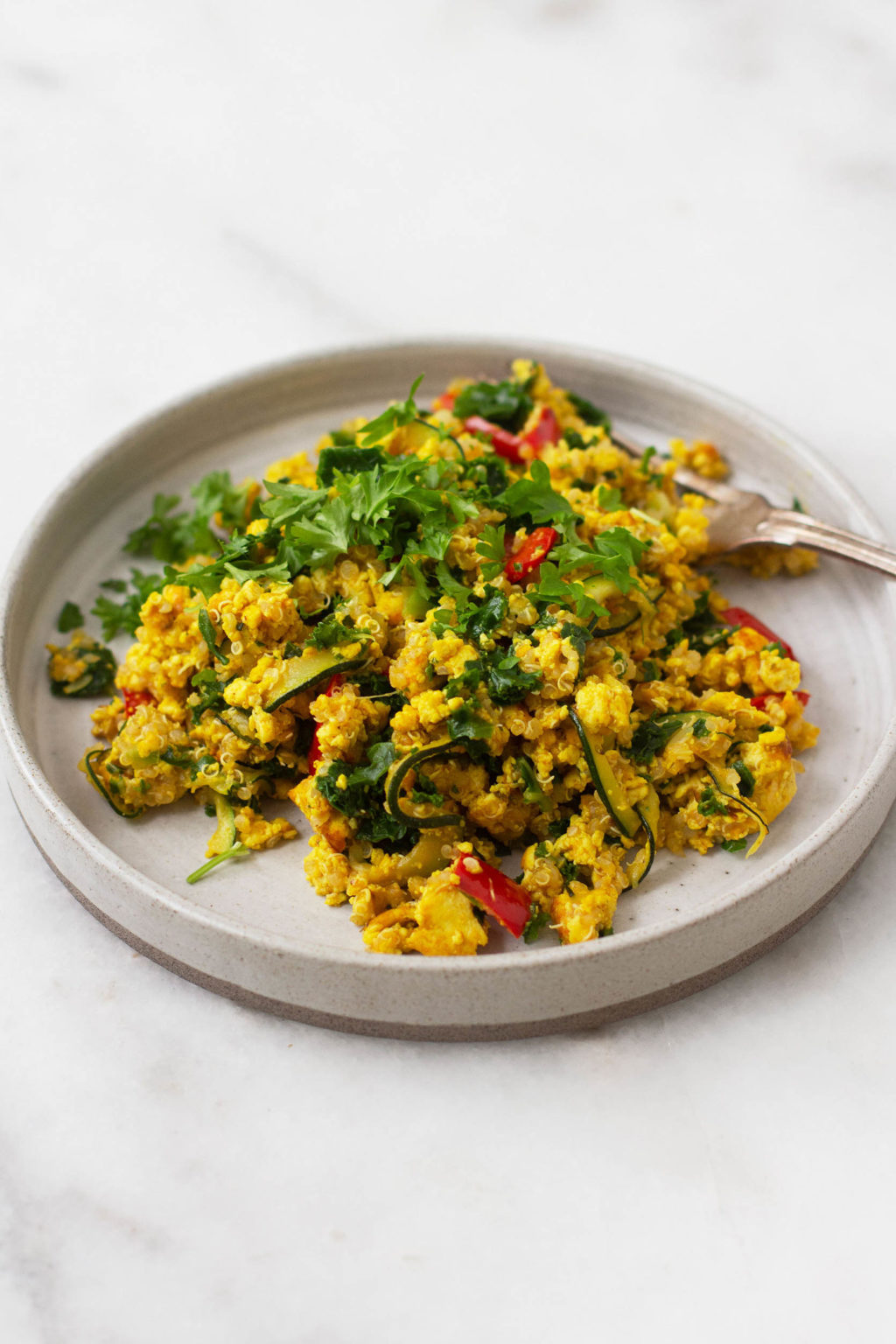 A vibrant, colorful plate of vegan tofu vegetable scramble with quinoa folded in. Topped with fresh, chopped herbs.