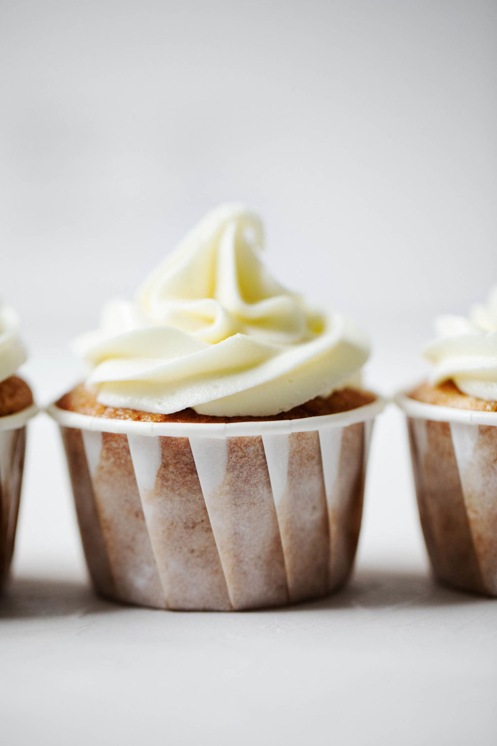Plant based cider cupcakes with cream cheese frosting, lined up in a neat row.