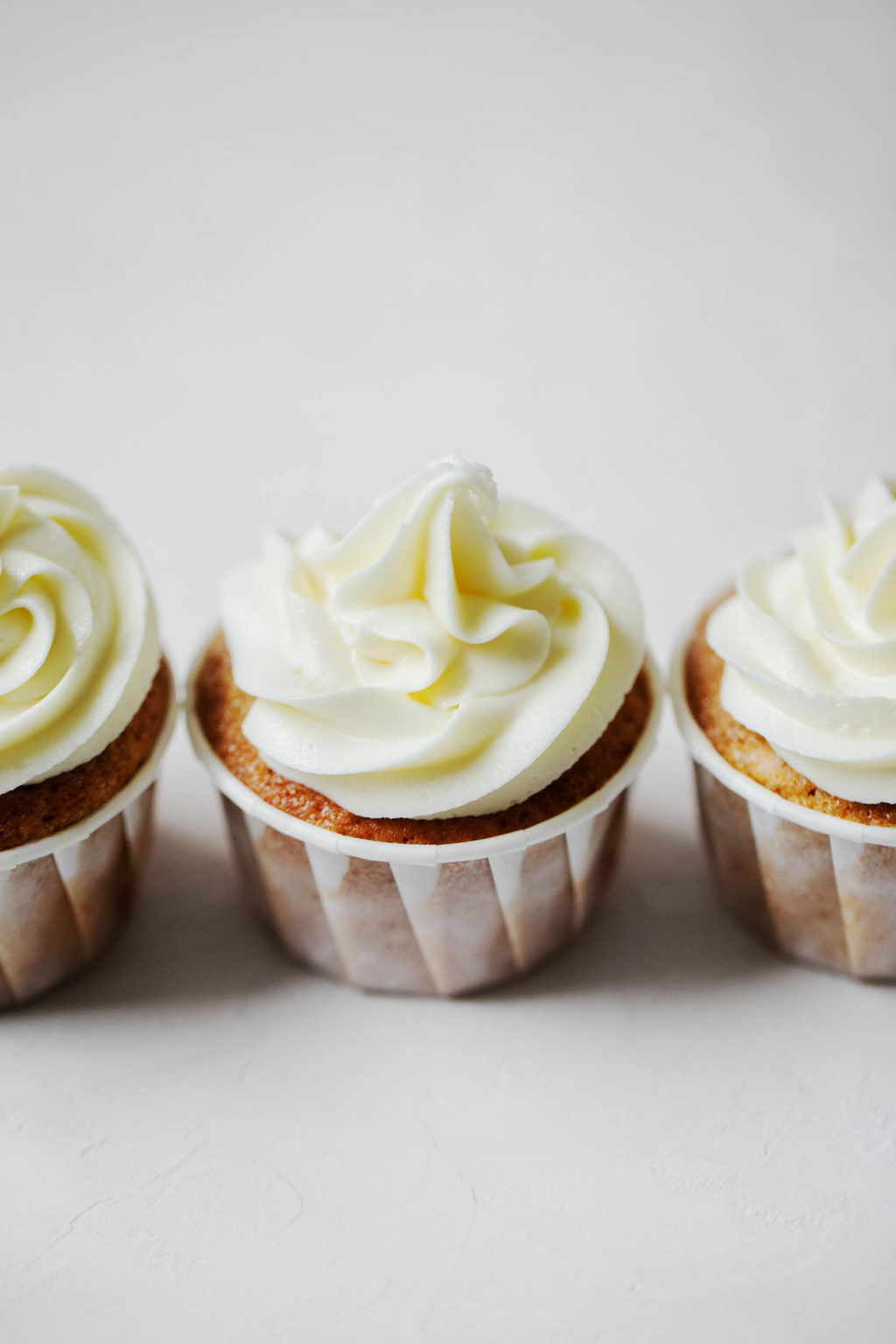 Three frosted vegan apple cider cupcakes, lined up in a row.