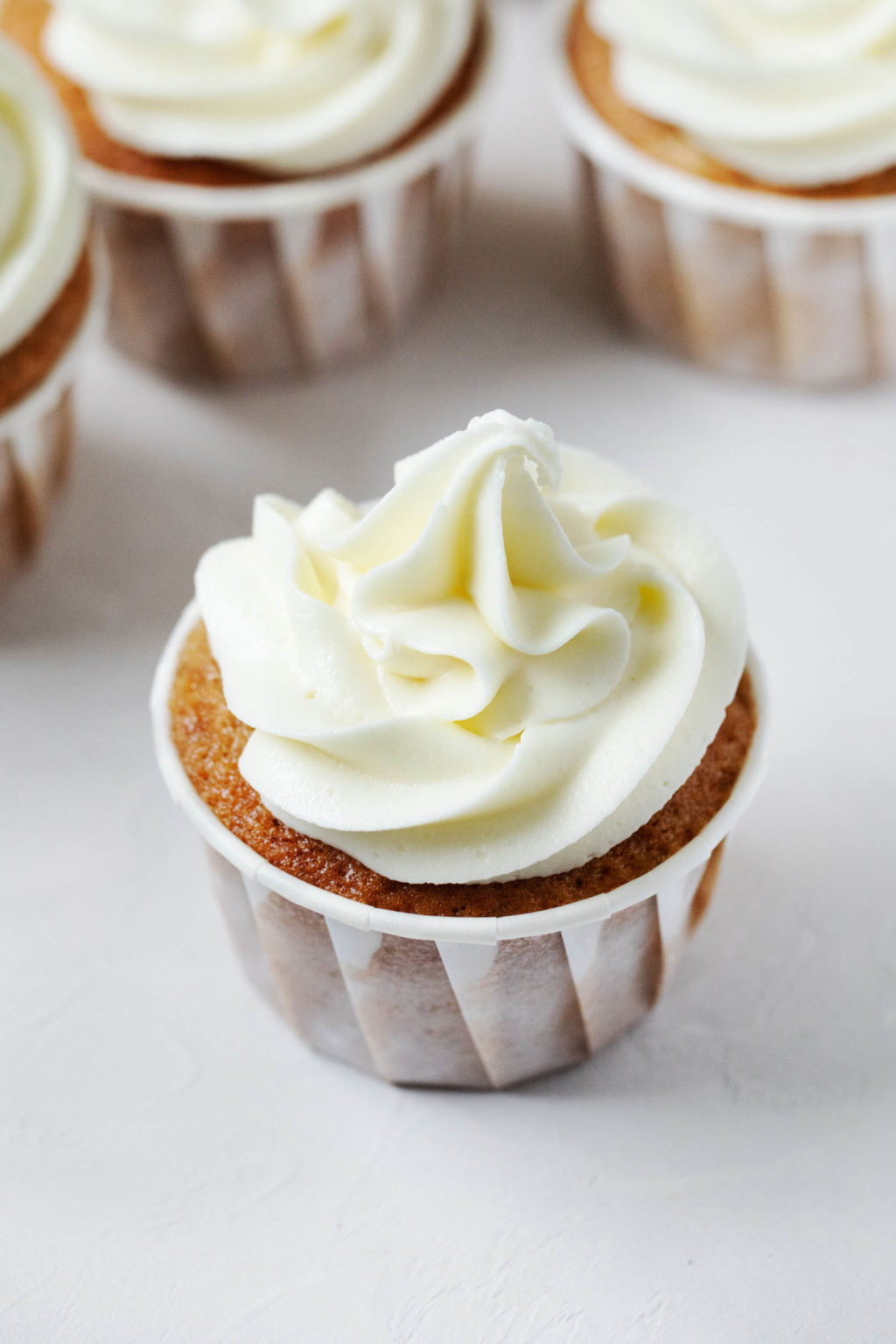 An angled photograph of apple cider cupcakes, each piped with a big swirl of dairy free frosting.