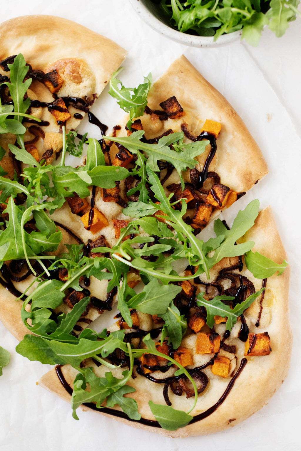 An overhead photo of vegan butternut red onion pizza, garnished generously with fresh arugula and drizzled with balsamic vinegar.