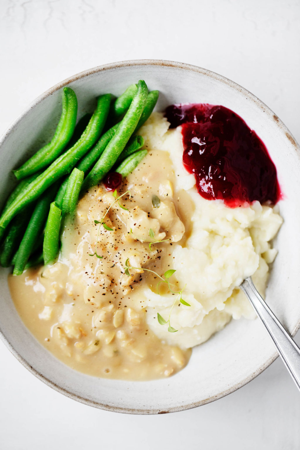 A bowl of vegan holiday food, including mashed potatoes, tempeh and gravy, green beans, and a little scoop of cranberry sauce.