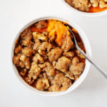 A small ramekin holds a single serving of vegan sweet potato casserole.