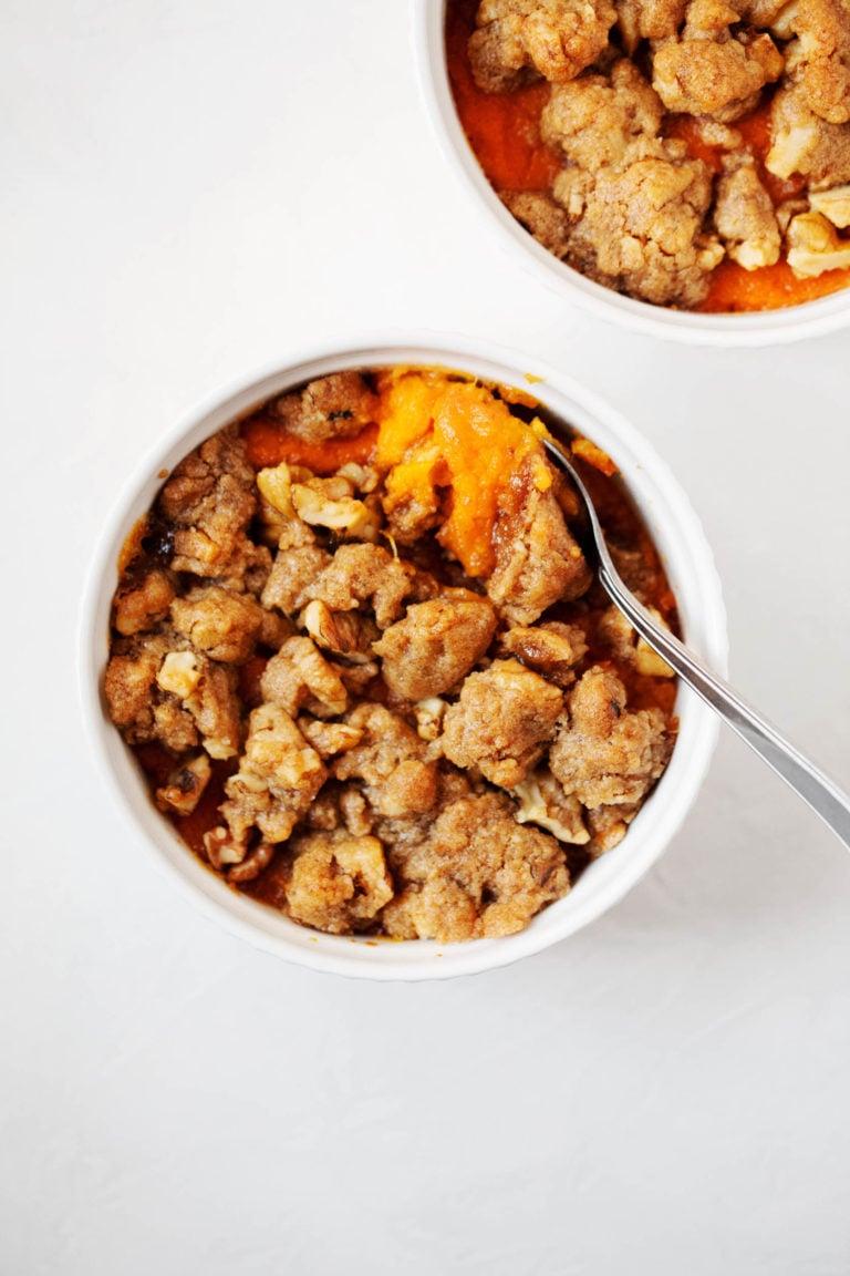 A small ramekin holds a single serving of vegan sweet potato casserole.