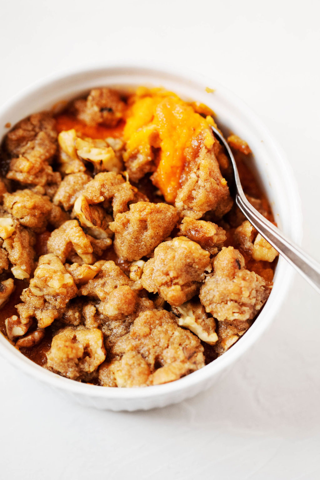 A small, circular baking dish is filled with a miniature version of vegan sweet potato casserole.