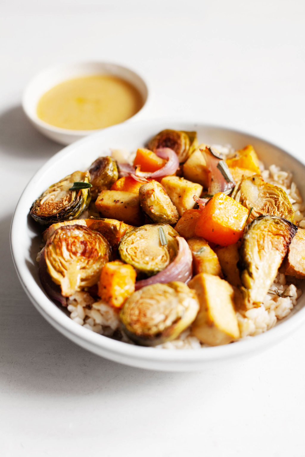 A serving bowl of seasonal, autumn produce is served over rice and accompanied by a small bowl of vinaigrette on the side.