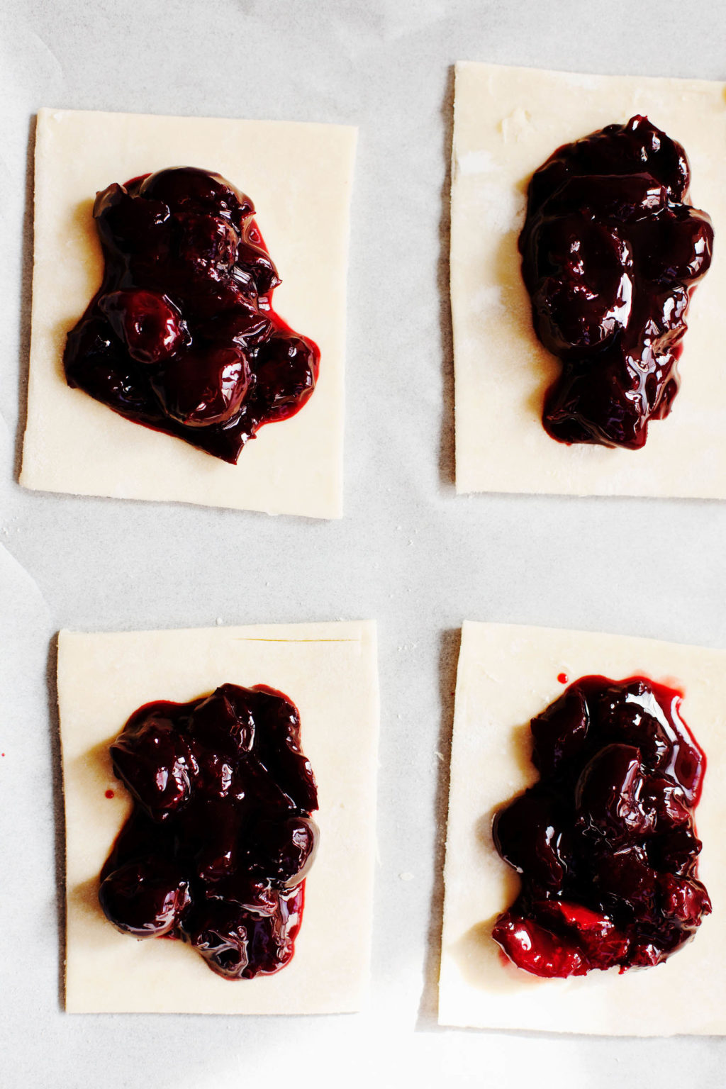 Vegan pastry pies on a parchment sheet, cut into rectangles. Each rectangle is topped with a sweet cherry filling.