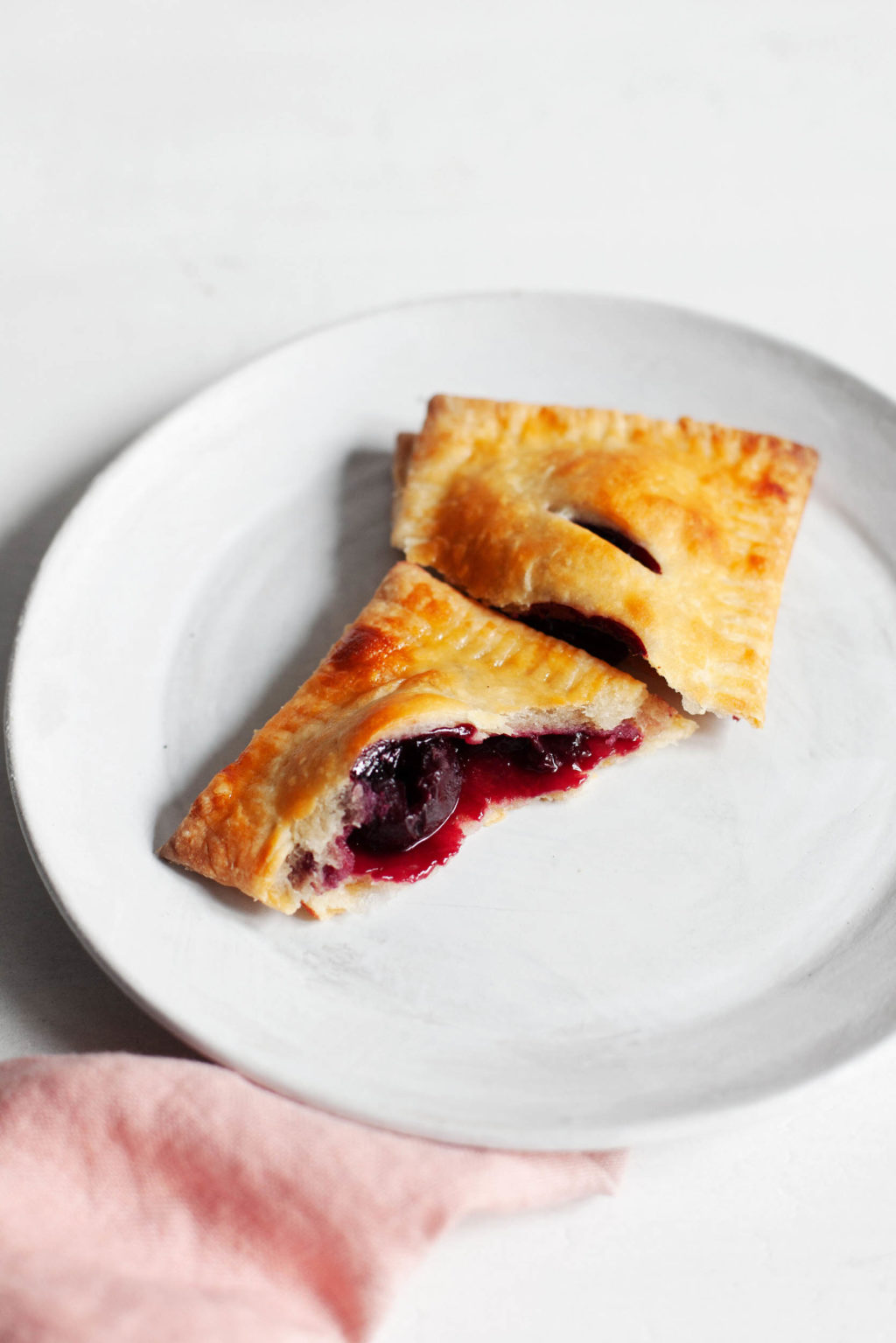 A vegan sweet cherry hand pie, freshly baked and broken apart for eating, rests on a dessert plate with a pink napkin nearby.