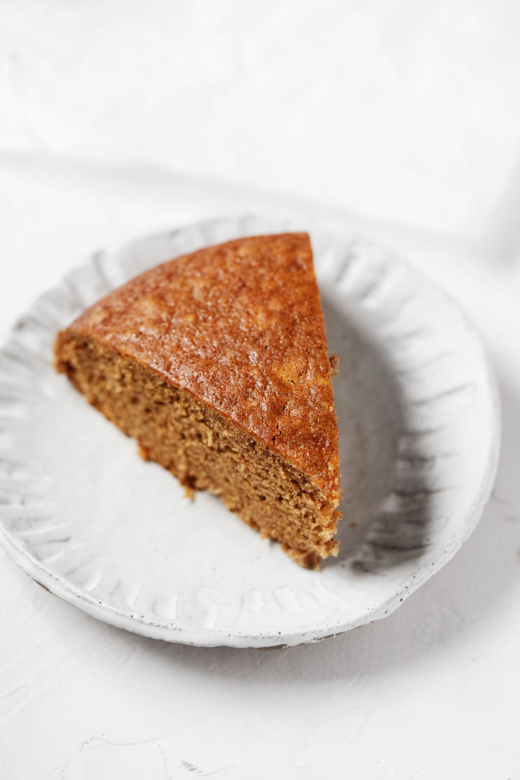 A golden brown slice of vegan gingerbread cake is laid out on a small dessert plate.