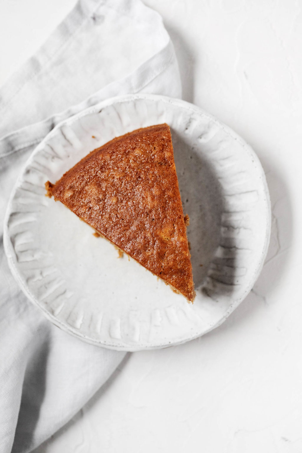 An overhead image of a triangular slice of gingerbread, laid out on a dessert plate with a gray napkin.
