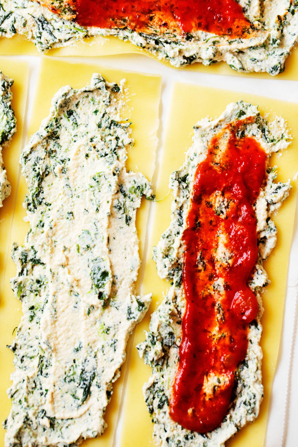 A few lasagna sheets are laid out on a work surface. Each is covered with plant-based ricotta, spinach, and marinara sauce.