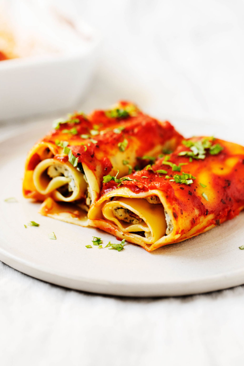 Two long, flat noodles have been filled with plant-based ricotta and spinach, topped with sauce, and rolled up.