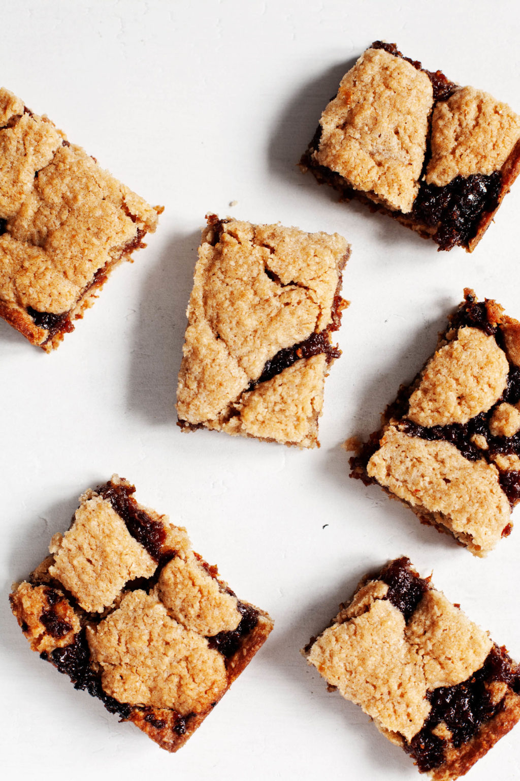 Freshly baked, whole wheat raisin bars are laid out on a bright white surface.