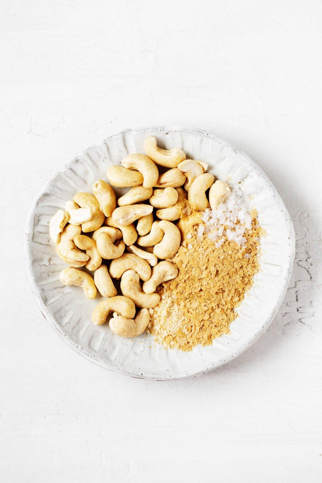 Un pequeño plato de porcelana contiene anacardos crudos y levadura nutricional.