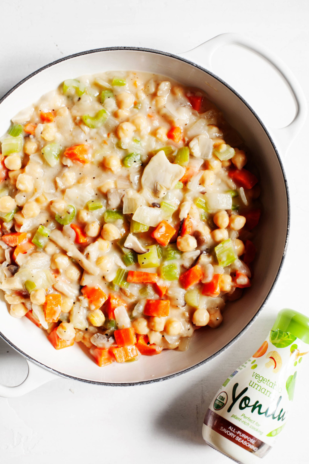 A round casserole dish filled with vegetables and beans in a creamy sauce is accompanied by a liquid seasoning in its packaging.