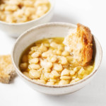 Two matching white bowls were filled with beans, soup and pieces of fresh bread.