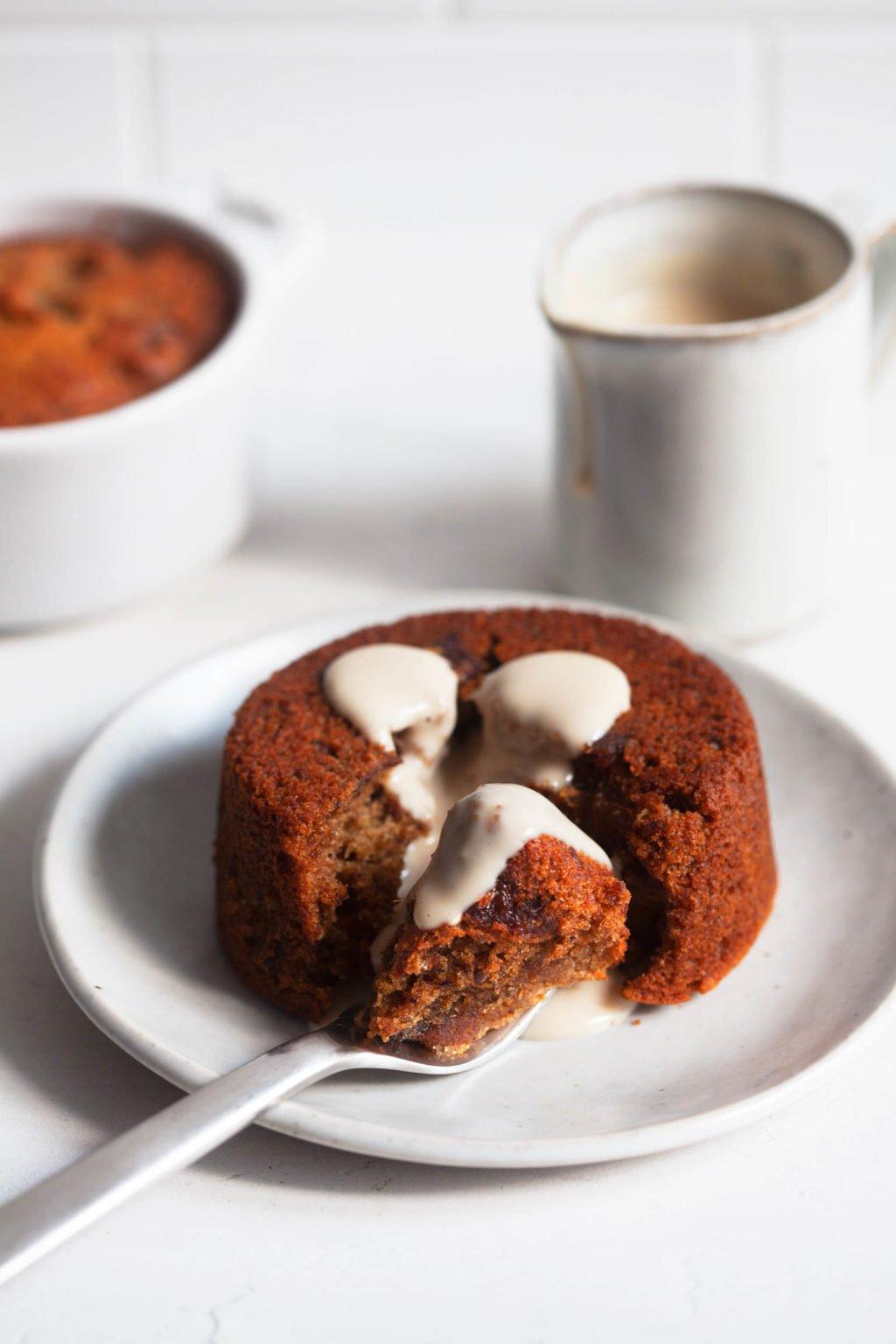 El budín de caramelo pegajoso vegano está en un pequeño plato de postre, con salsa de crema de anacardos y otro molde de pudín de fondo.