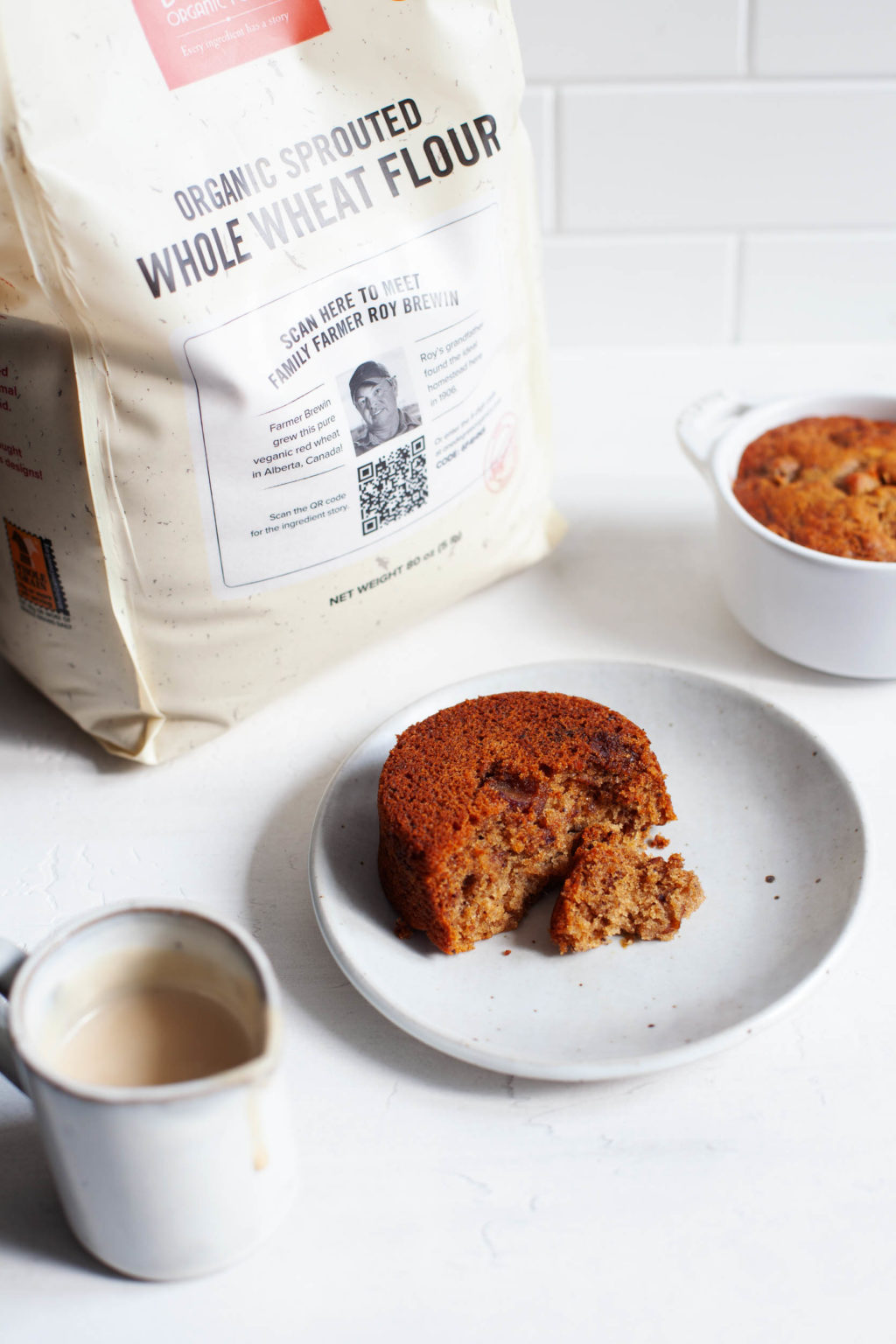A bag of whole grain flour has been used to make a few small, round cakes, which are positioned on dessert plates.
