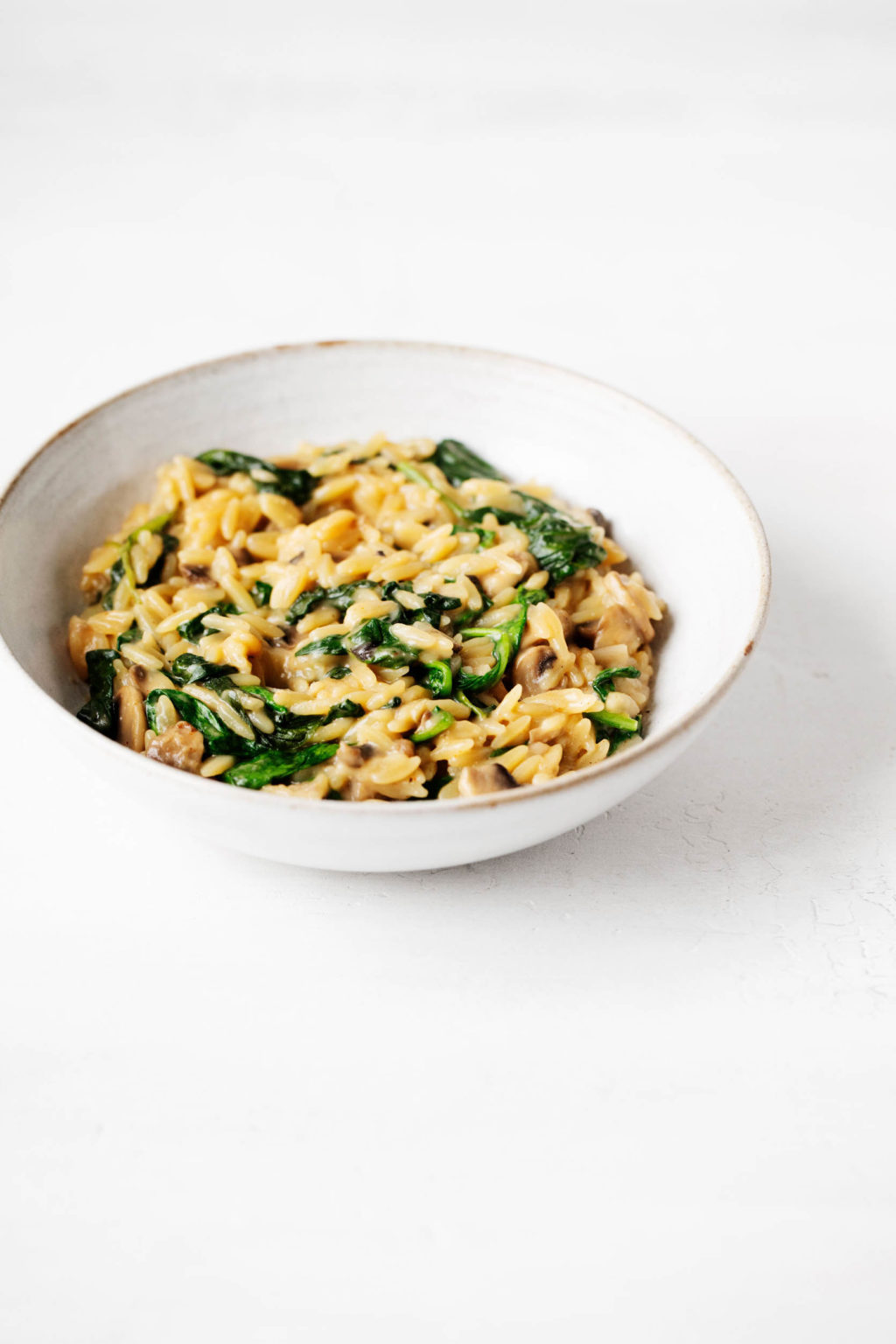 A white bowl with a pale brown rim has been filled with a mixture of small pasta and greens.