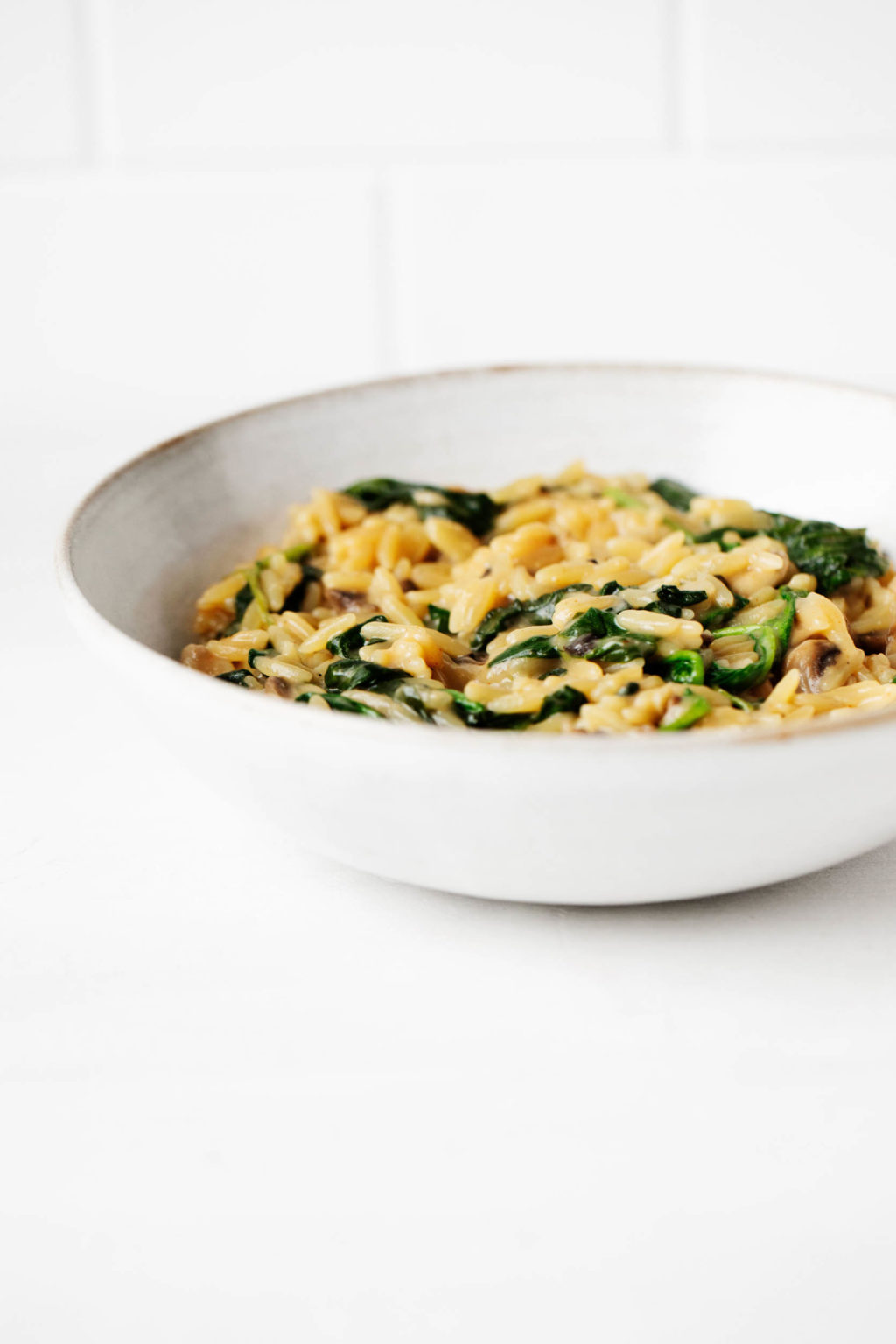 A round, white bowl has been filled with orzo and spinach. It's resting on a bright white surface.