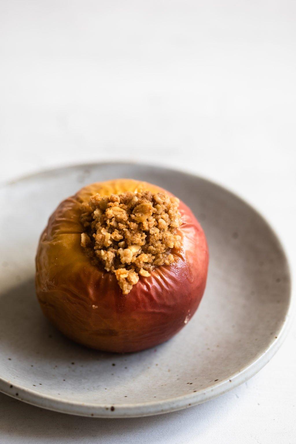 Una sola manzana roja y dorada rellena y horneada descansa sobre un plato de postre de cerámica gris claro.