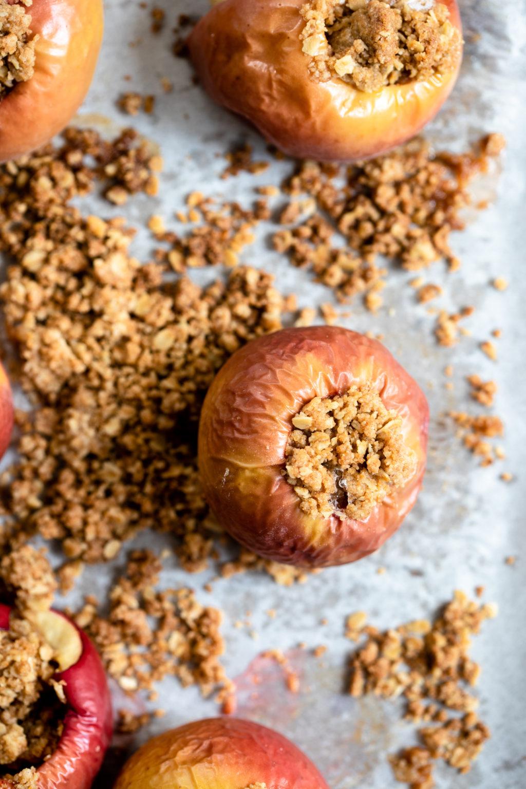 Una fotografía aérea de manzanas horneadas y rellenas, que aún descansan sobre una bandeja para hornear forrada de pergamino.