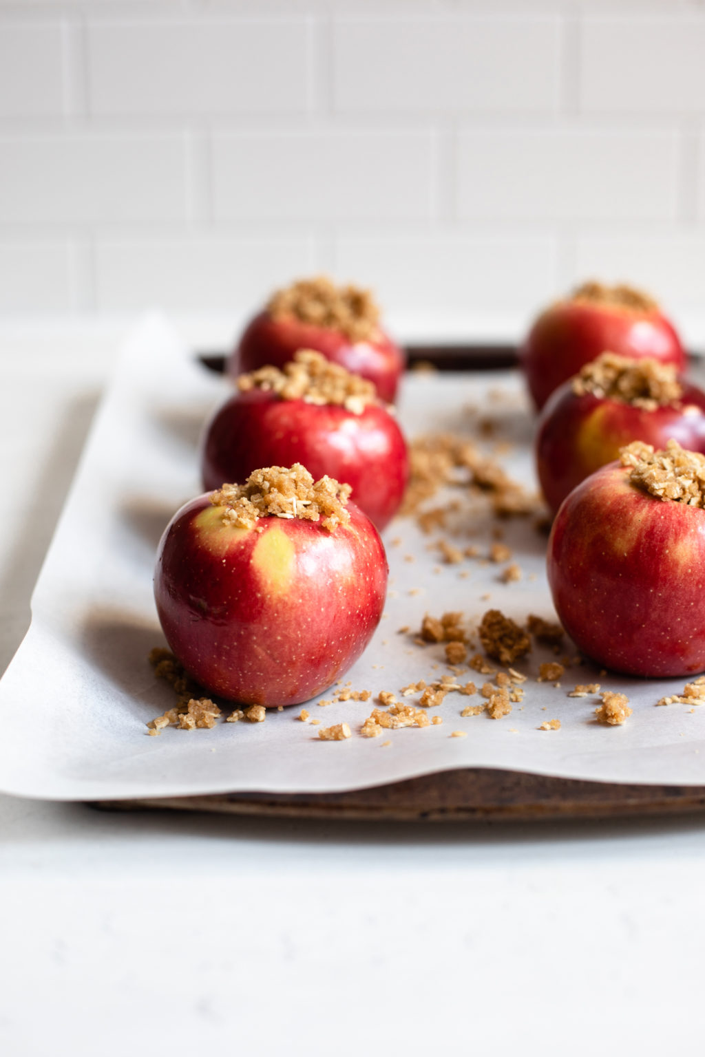 A baking sheet is covered with parchment and bright red apples that have been stuffed with a filling of oats, flour, and brown sugar.