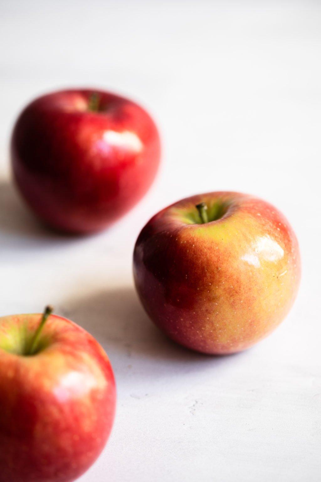 Una fotografía de tres manzanas rojas y doradas sobre un fondo blanco brillante.