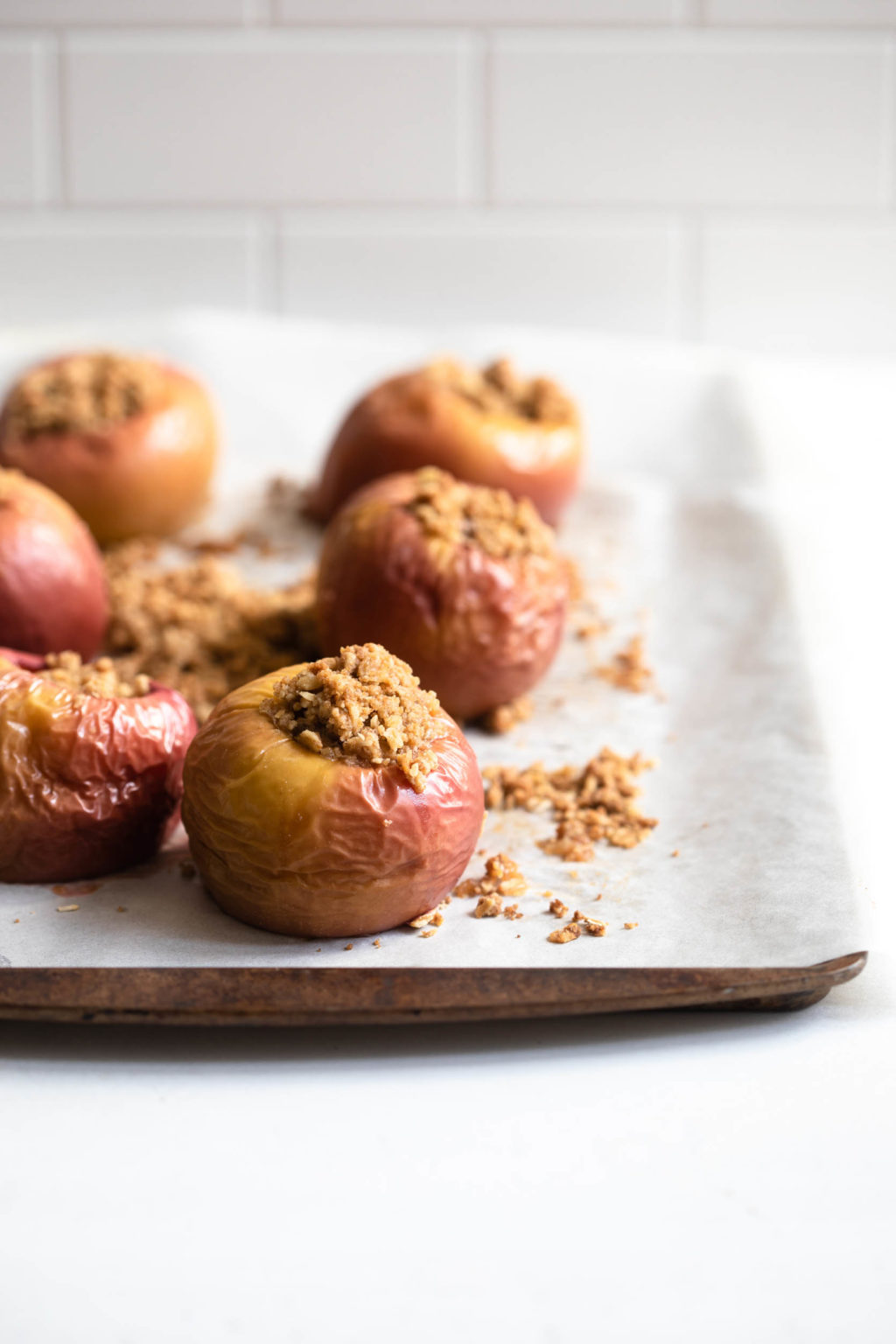 A parchment lined baking sheet holds six baked stuffed apples, with streusel crumbs on the parchment.