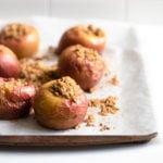 Una bandeja para hornear forrada de pergamino contiene seis manzanas rellenas horneadas, con migas de streusel en el pergamino.