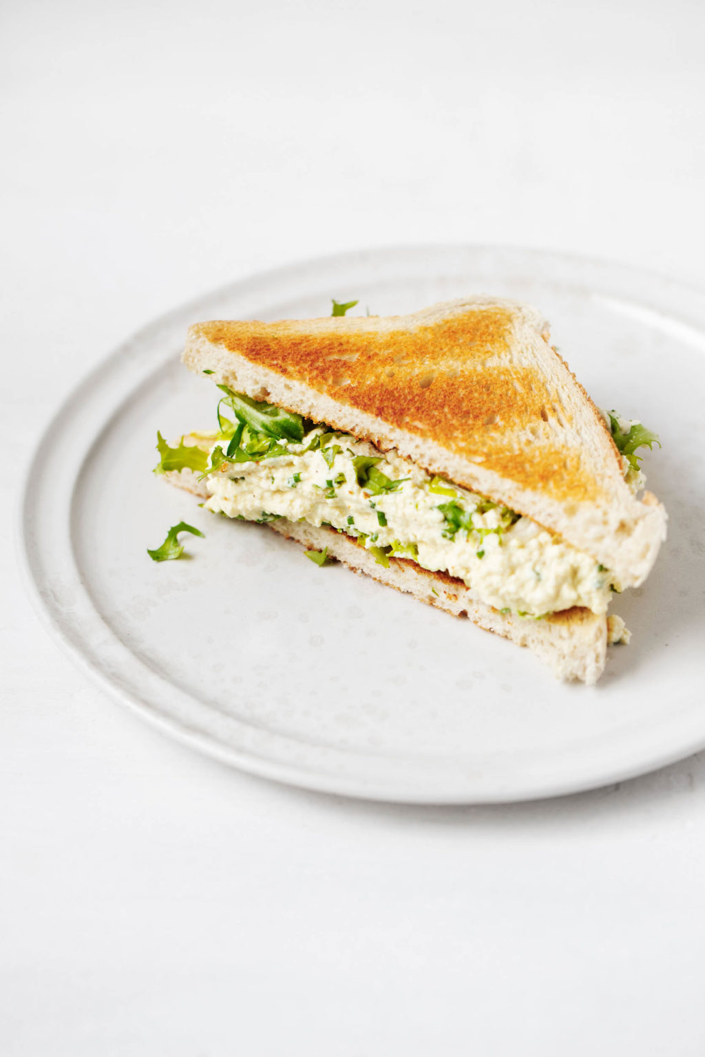 An angled photograph of a white plate that has been topped with half of a tofu egg salad sandwich and fresh greens.